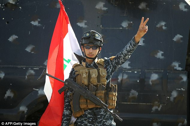 This soldier held up two fingers to celebrate the success of the offensive against the Islamic State, which has held the city for the past three years