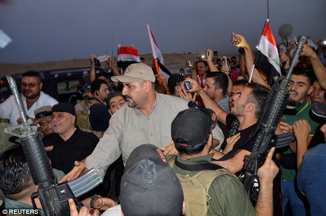Iraqi Prime Minister Haider al-Abadi is pictured in Mosul, Iraq on July 9 as civilians wave flags and celebrate ISIS' defeat