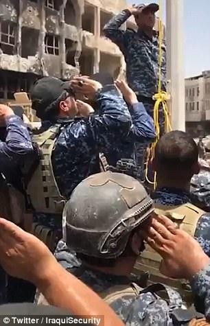 """Las tropas gubernamentales están presionando para recuperar el territorio restante en poder del grupo terrorista en la ciudad después de que el líder del país celebrara la """"victoria"""" sobre los yihadistas. Se representan levantando una bandera iraquí en la ciudad"""