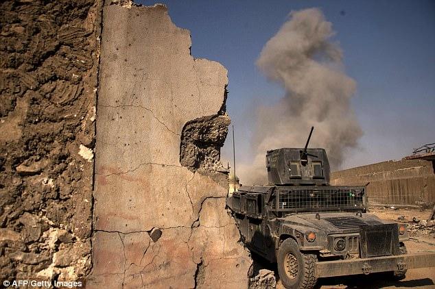 Una pluma de humo se eleva desde la ciudad vieja de Mosul, donde la lucha esporádica todavía se llevaba a cabo el lunes por la tarde