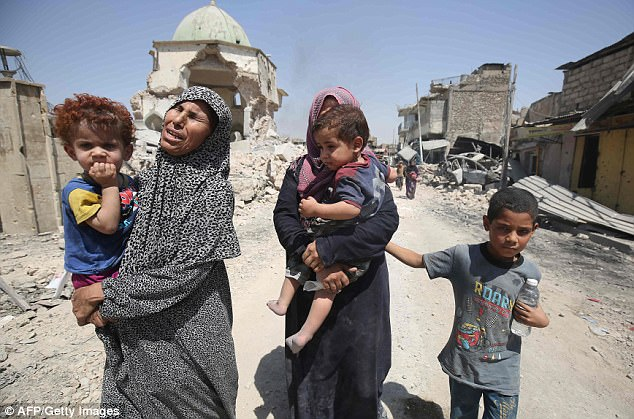Children have revealed how they were forced by ISIS fanatics to mutilate prisoners in Iraq. Iraqi women are pictured carrying yongsters to safety in Mosul's Old City last week
