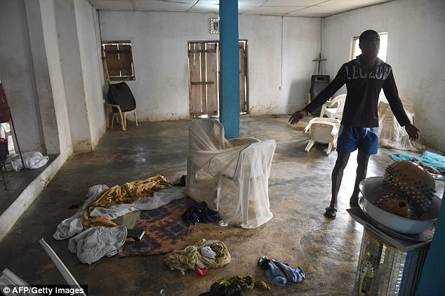 Pictured: A man points to blood stained clothes, drums, bibles and hymn books on the bare floor in Lagos