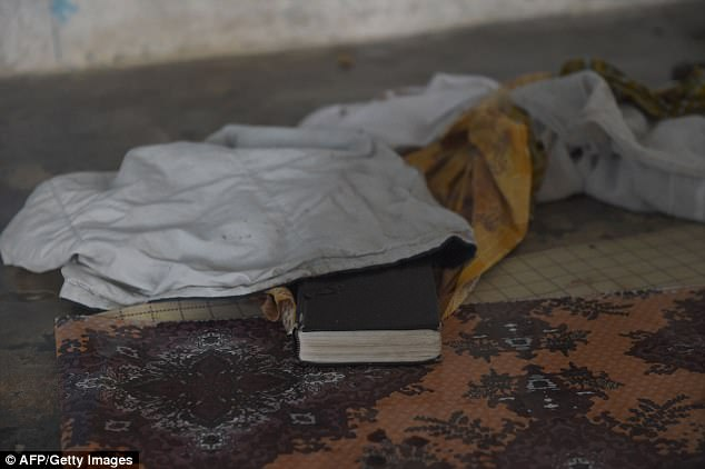 Pictured: A Bible covered by blood stained clothes lies on the floor in the Lagos church