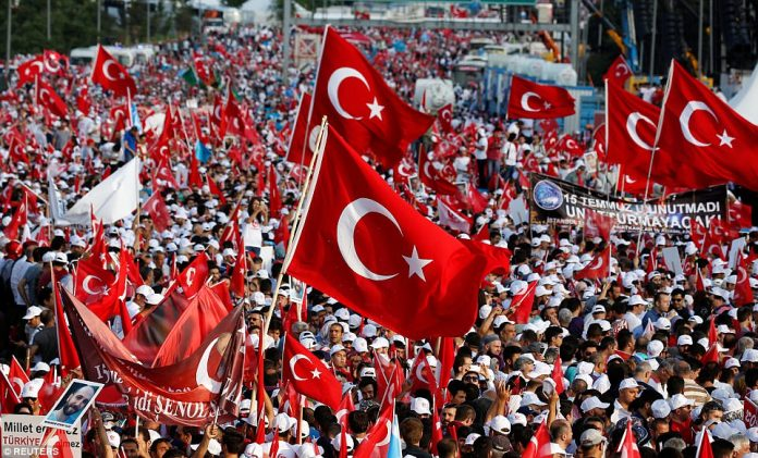 People wave Turkey's national flags as they attend a ceremony marking the first anniversary of the attempted coup at the Bosphorus Bridge in Istanbul. The bridge was the scene of clashes between civilians and soldiers in tanks. At least 30 people died there and more than 2,000 were injured across Turkey in the struggle. Thirty-five coup plotters were also killed