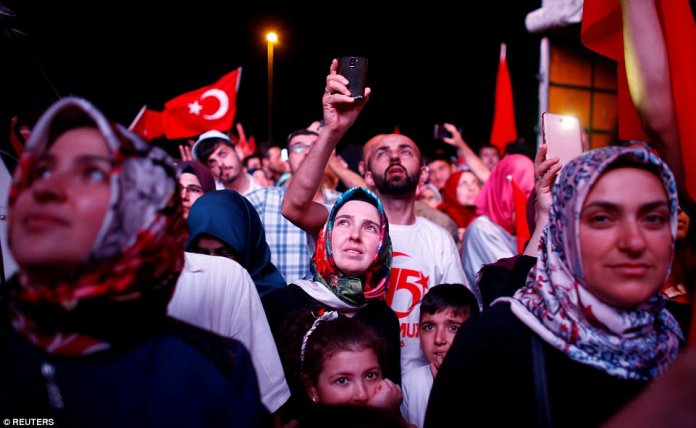 People listen to the speech of Turkey's President Tayyip Erdogan during a ceremony marking the first anniversary of the attempted coup at the Bosphorus Bridge in Istanbul