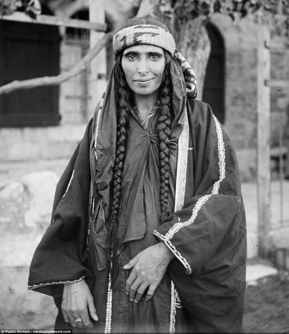 Photographs show Bedouins - including this woman with waist-length hair and traditional clothes - living their day to day lives, gathering around makeshift tents and huts