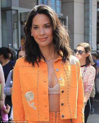Cheeky: Olivia flashed some cleavage by wearing just a white bra under an orange cropped jacket that she left unfastened