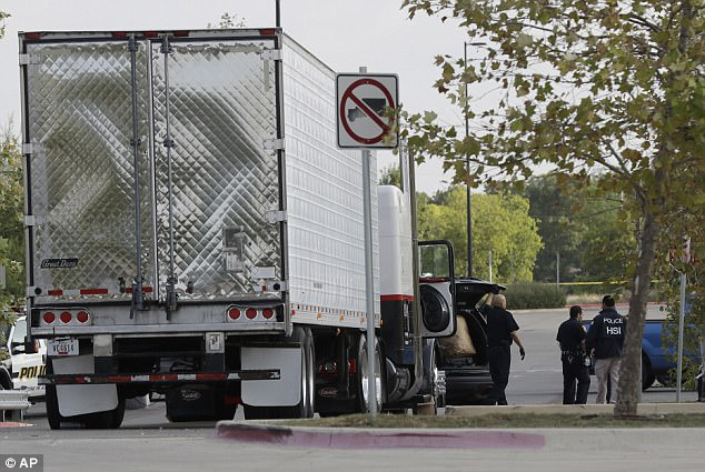The employee gave the person the water and then called police, and when officers arrived they found the eight people - all men - dead in the back of the trailer, police Chief McManus said (Pictured, a police officer is seen shining a light into the back of the truck where eight people were found dead)