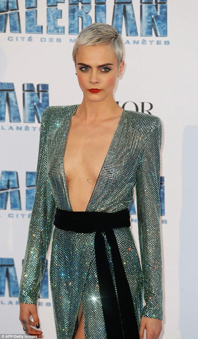 Sassy in sequins: Cara, 24, looked equally as chic in a plunging silver gown adorned with hundreds of glittering sequins