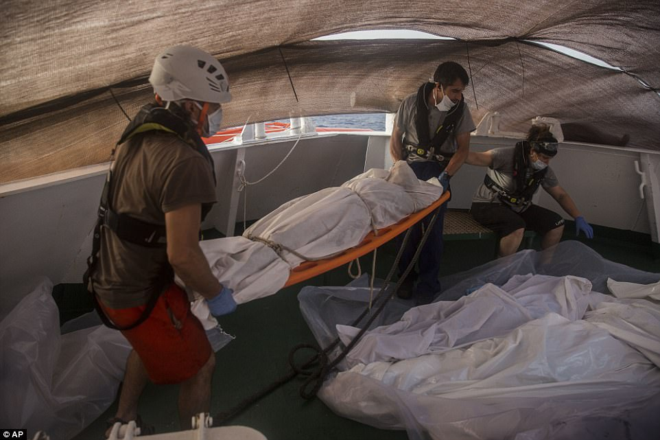 Los trabajadores de ayuda llevan el cadáver de un emigrante fuera del barco en una camilla anaranjada mientras que otros cuerpos se amontonan para arriba para ser carted lejos