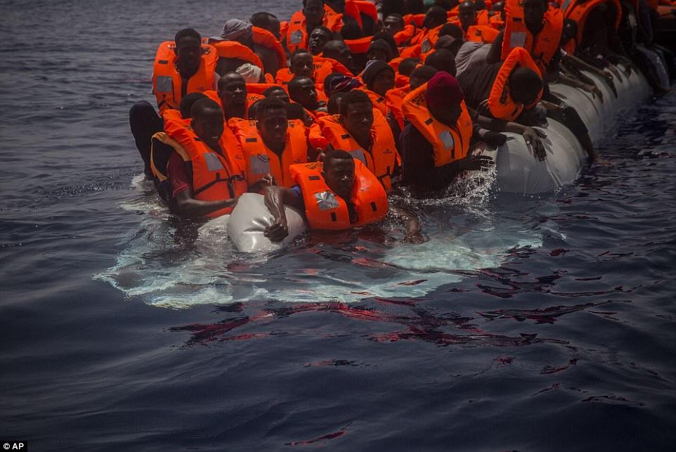 Docenas de inmigrantes parecen asustados como el bote de goma gris que están viajando sobre miradas destinadas a hundirse en el fondo del mar Mediterráneo