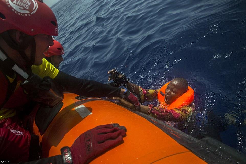 Un emigrante africano con una camisa modelada se refugia desesperadamente en un rescate sucio cuando los trabajadores de caridad intentan arrastrarlo a bordo