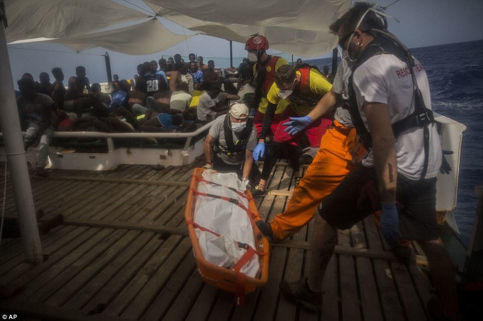 Un cadáver es amarrado en una camilla y llevado de las decenas de migrantes sentados en el bote de rescate en el Med