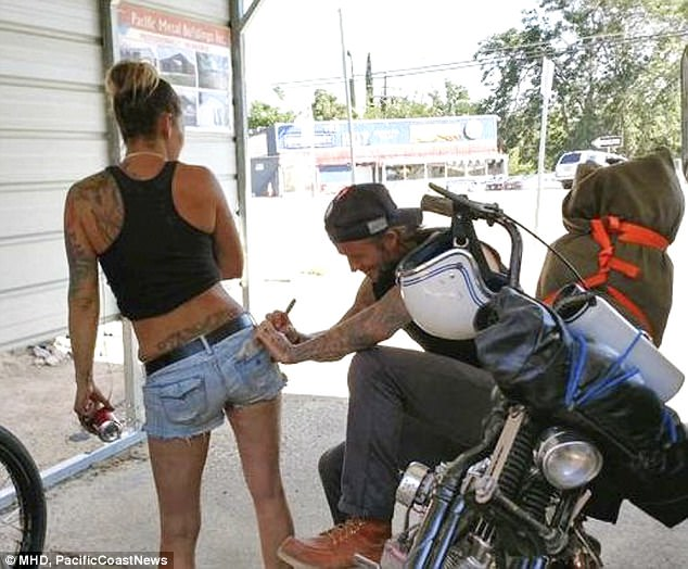 Cheeky: David Beckham was spotted penning his autograph on a cheeky girl's bottom during his motorcycle road trip in Kernville, California on Sunday