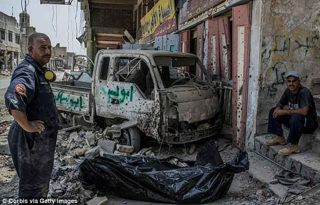 Two Iraqi Civil Defence workers next to two bodybags lying on the rubble in front of a battered truck full of bullet holes
