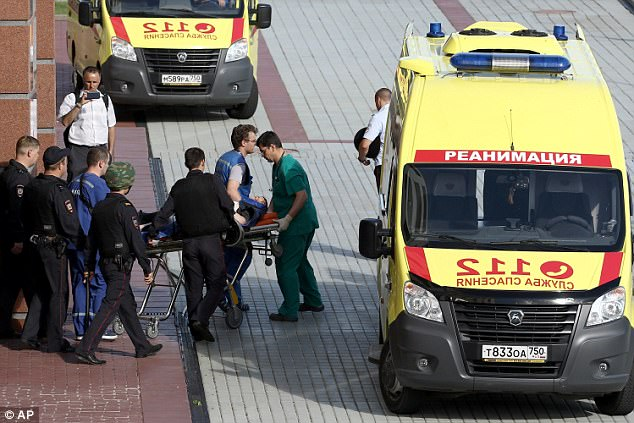 Medics rush a casualty in to a waiting ambulance after the shootout at a Moscow court this afternoon