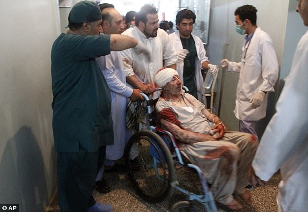 Relatives assist a wounded man in a hospital after a suicide attack onthe Jawadya mosque on Tuesday evening