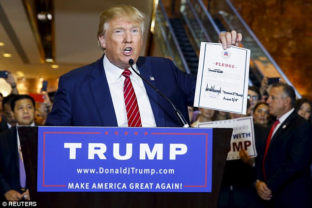 Then-candidate Donald Trump holds up a signed pledge during a press availability at Trump Tower in Manhattan, New York September 3, 2015