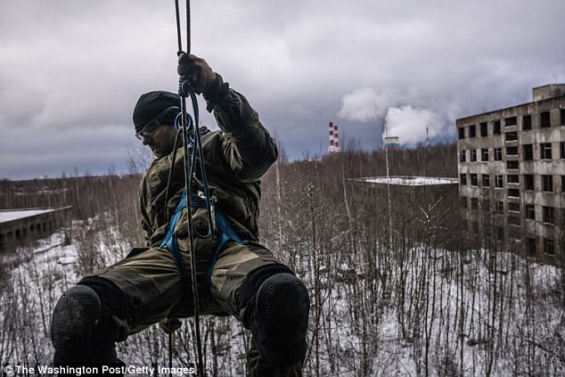 Russian extremists are training people from Europe to use machine guns at a paramilitary course where fanatics prepare for 'the collapse of civilization', it has been claimed. A man is pictured abseiling at the camp last year