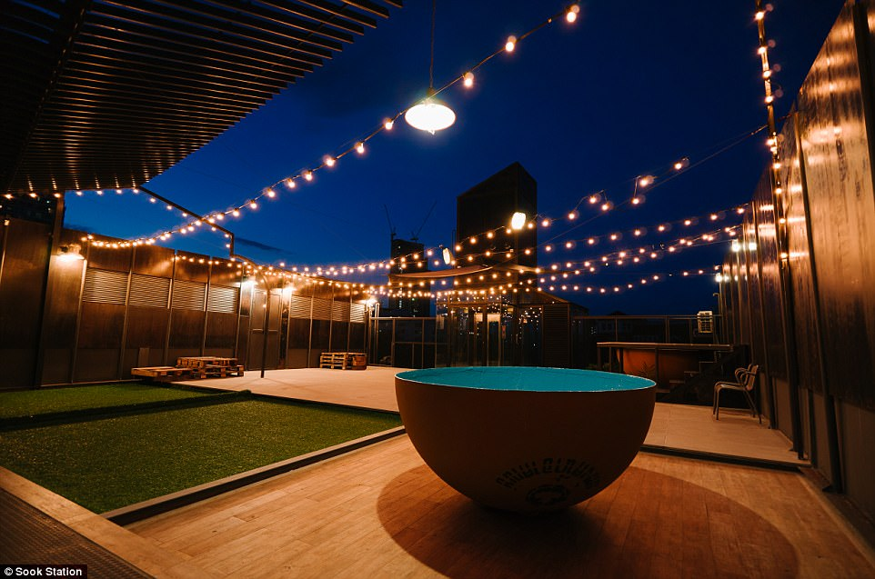 Home comforts: Outside, there are carefully manicured lawns decorated with party lights