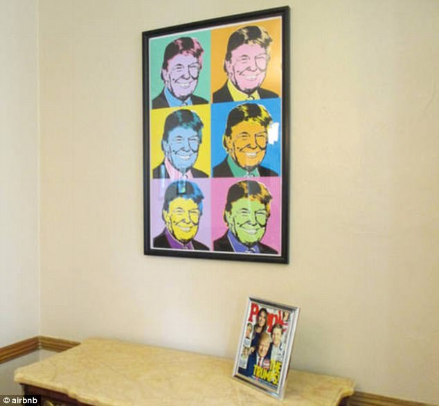 One side table in the home features a People Magazine cover with the Trump family on the front and sits below another framed art piece of the president