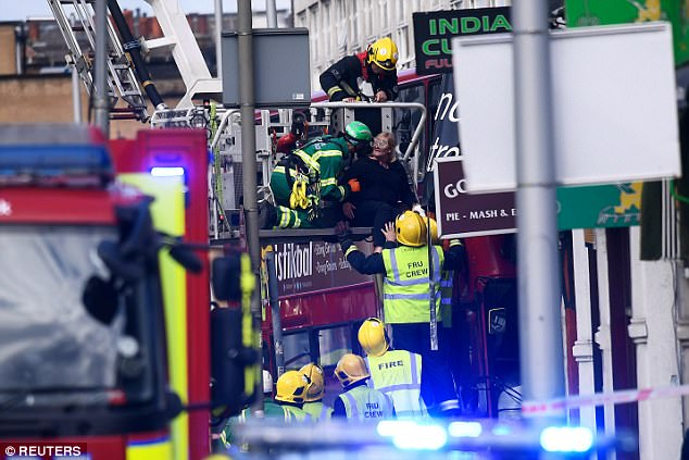 The woman is helped out of the bus after she was trapped on the top floor following the crash