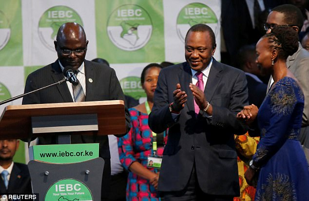 Incumbent President Uhuru Kenyatta applauds after he was announced winner of the presidential election at the IEBC National Tallying centre