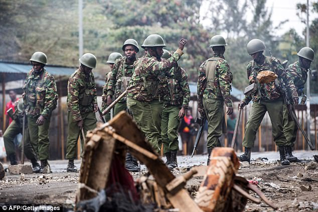 Kenyan police officers clear debris and stones from a barricaded road after a protest by supporters of the National Super Alliance (NASA) opposition coalition presidential candidate on August 11