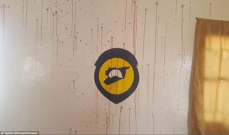 Esta inquietante imagen muestra las paredes salpicadas de sangre de la habitación en la que se disparó a los voluntarios.  El logotipo de Cascos Blancos se ve en el centro