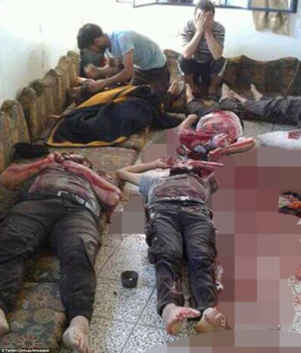 Una imagen del momento en que se descubrieron los cadáveres muestra los cadáveres ensangrentados de los trabajadores uniformados rodeados de colegas afligidos que abrochan la cabeza en sus manos