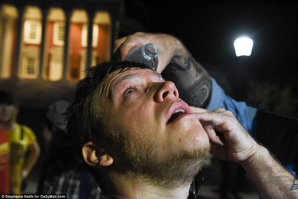 An activist reacts to pepper spray in his eyes during a torch lit march through the University of Virginia campus