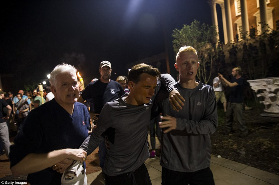 A man who was pepper-sprayed is helped away from white supremacist marchers at the University of Virginia campus