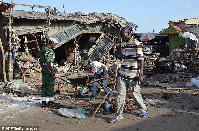 """Según los autores del informe, es menos probable que las mujeres y los niños sean buscados, lo que los convierte en objetivos más fáciles.  Pueden ocultar bombas mucho más fácilmente a simple vista y los hombres a veces se visten como mujeres para que se les ofrezca el """"lujo"""" y resbalen fácilmente por la seguridad (foto: un hombre pasa por la escena de un bombardeo en el noreste de Nigeria)"""