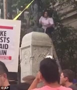 She can be seen in video showing the moments before the Confederate statue was toppled at the top of the monument (above).