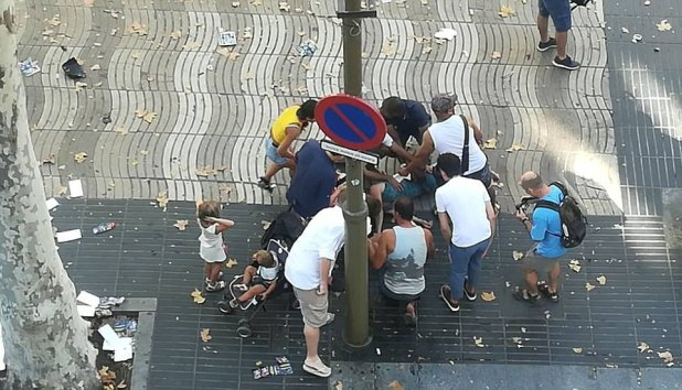 Pictured: People gather round a victim after the van drove into a crowd in Barcelona