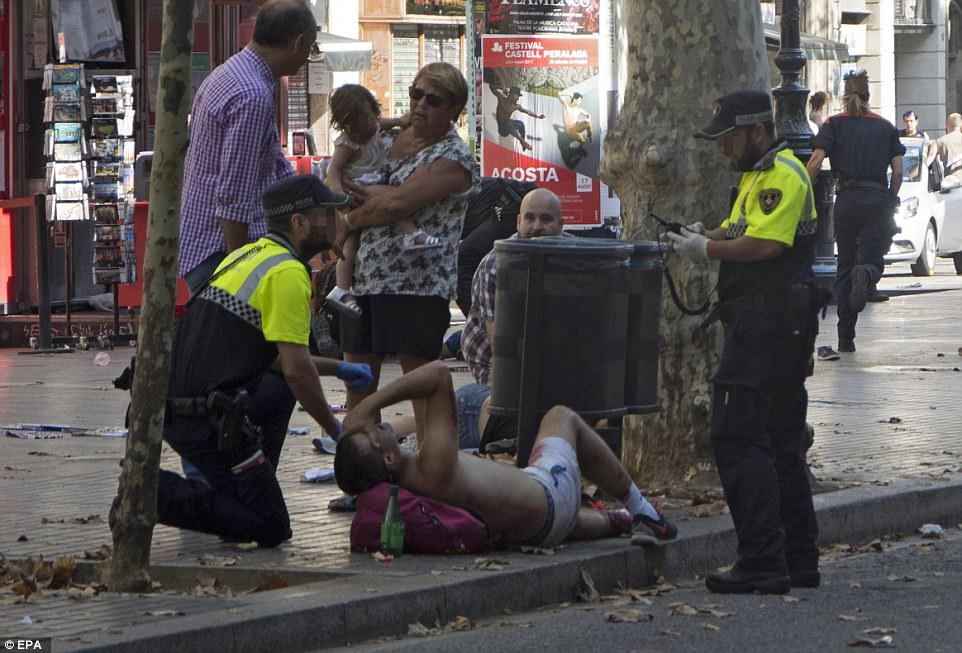 Pictured: A man lying on the street in Barcelona after the van ploughed into pedestrians along Las Ramblas