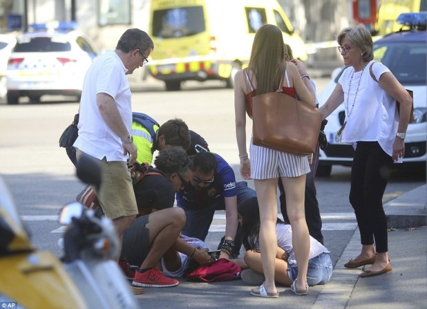Pictured: A woman lies injured on the pavement as paramedics offer treatment