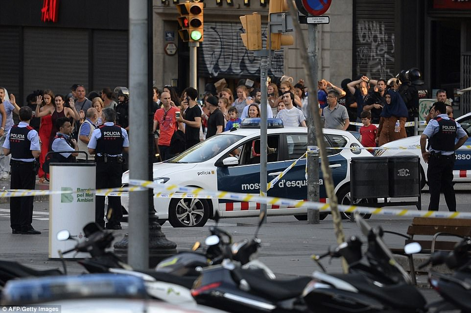 People are guided out of a fast food restaurant by police after the attack in Barcelona on Thursday afternoon