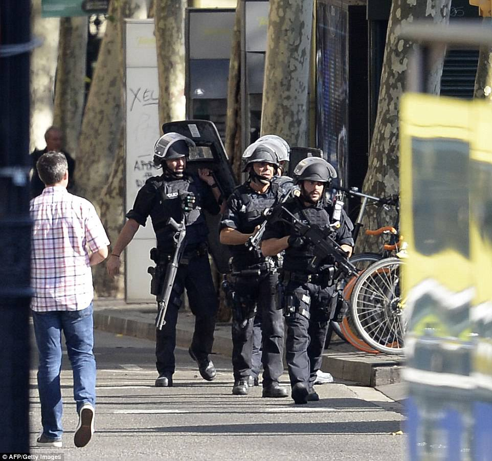 Armed policemen arrive in a cordoned-off area after a van ploughed into a crowd in Barcelona, killing at least 13 people yesterday