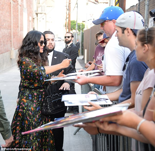 Crowd pleaser: The sprightly star stopped to sign fans autographs as she made her way into the studios