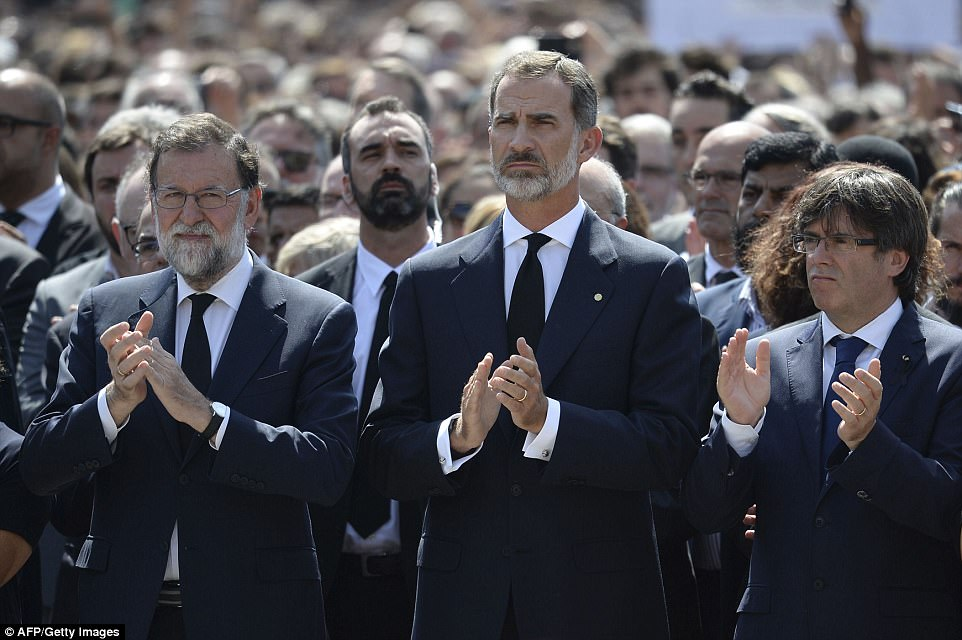 Spain's King Felipe VI (C), Spanish Prime Minister Mariano Rajoy (L) and President of Catalonia Carles Puigdemont applaud after observing a minute of silence for the victims in Barcelona today