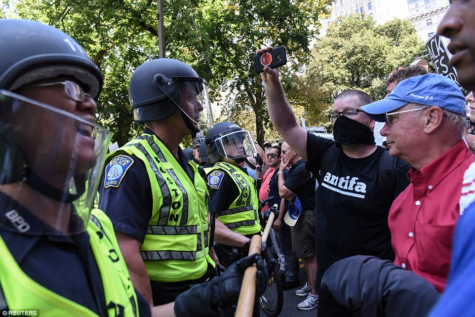 Police in riot helmets stand in the way of counter-protesters, as a man in an Antifa shirt records the standoff