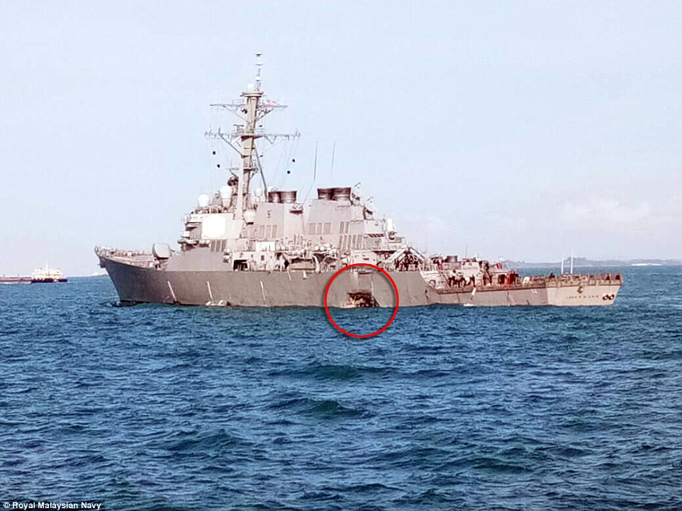 A picture of the US guided-missile destroyer after the collision shows the ship riding low in the water with a hole in its side near its waterline (pictured)