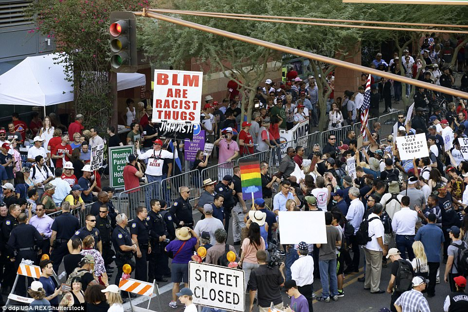 Police separate protesters from a line of Trump rally-goers that stretched six city blocks before the campaign rally outside the Phoenix Convention Center