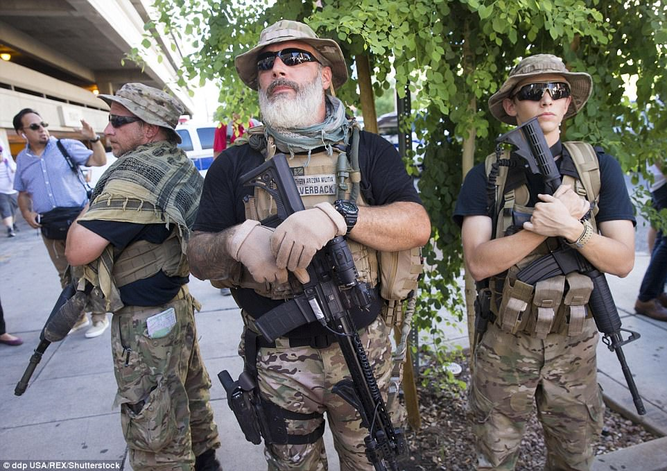 Southern Arizona Militia, a private group, stands guard outside the Phoenix Convention Center before the rally for Trump. Separately, a left-wing group called the John Brown Club brought its own armed watchdogs