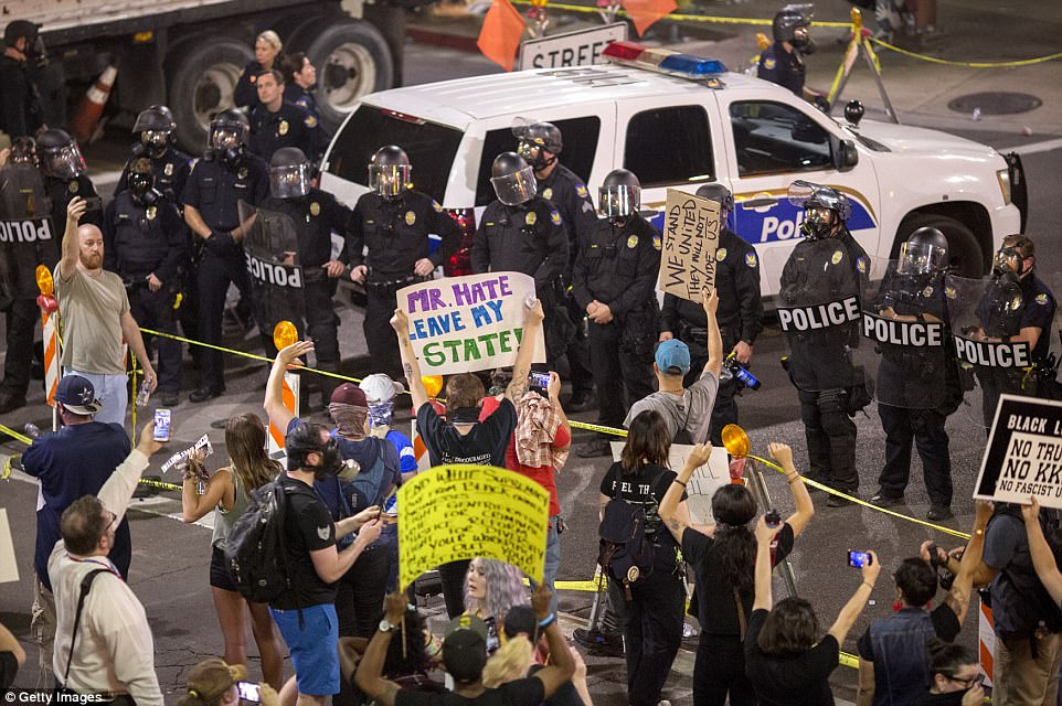 The unrest broke out after Trump swung through the city for a rally designed to fire up his base. Pictured: Police prepare to advance on protesters