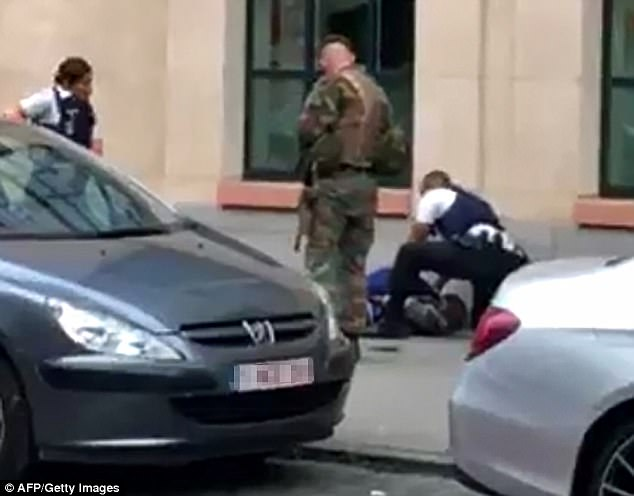 Police and a soldier are seen watching over the man who attacked troops in Brussels
