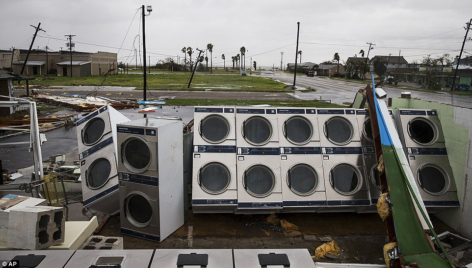 Several homes, businesses and schools in Rockport were severely damaged. Pictured: A laundromat's machines sit exposed in the elements after the building collapsed when Hurricane Harvey ripped through Rockport, Texas