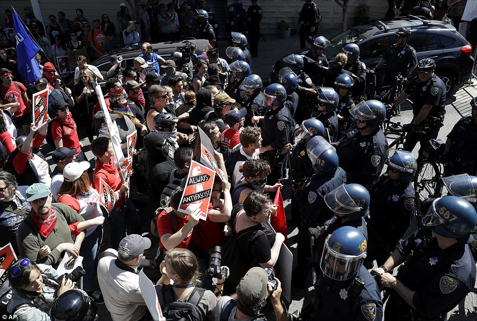 Face-off: Protesters confront San Francisco Police officers outside of Alamo Square Park in San Francisco, Saturday