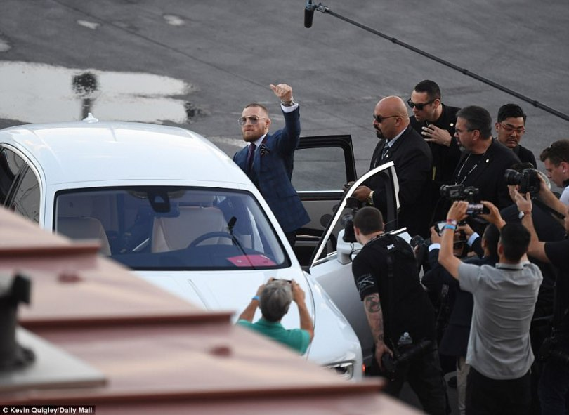 McGregor gives the thumbs up as he climbs out a white Rolls-Royce and prepares to make his way inside the Las Vegas venue